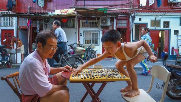 2018 年7 月19 日,上海老城厢望云路,一位6 岁的小男孩在和爷爷对弈。王溶江 摄